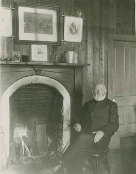 William Duncan sitting by his fireplace